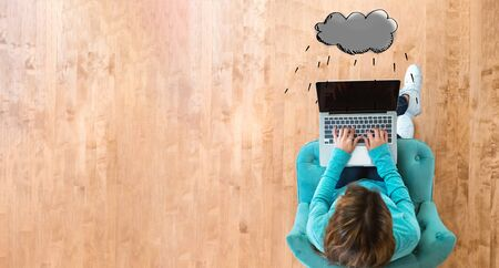 Rain cloud with woman using her laptop computer