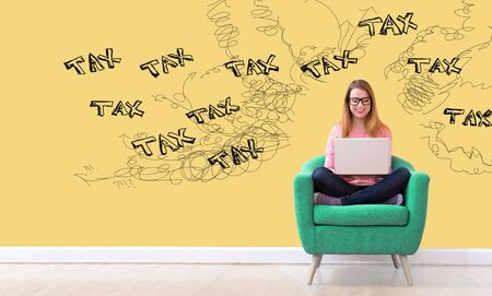 Tax problem theme with young woman using her laptop in a chair Stock Photo