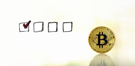 Checklist with a gold bitcoin cryptocurrency coin Reklamní fotografie - 128757630