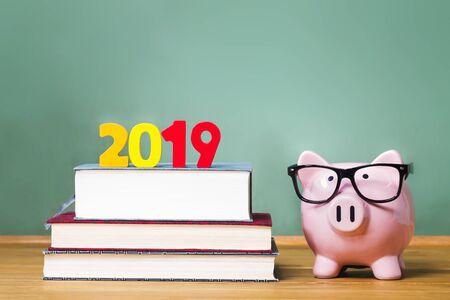 Tema de la clase de 2019 con libros de texto y alcancía con gafas sobre fondo de pizarra verde
