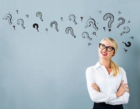 Vraagtekens met jonge vrouw in een nadenkend gezicht Stockfoto