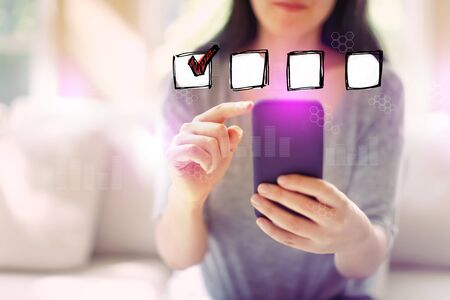 Checklist with woman using her smartphone in a living room Banco de Imagens