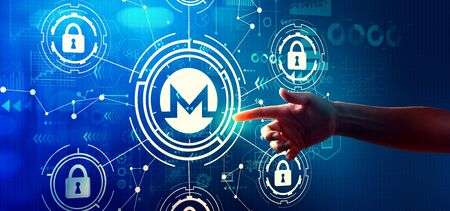Monero cryptocurrency security theme with hand pressing a button on a technology screen Stock Photo