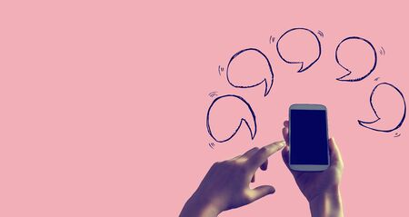 Speech bubbles with person holding a white smartphone 写真素材 - 128821887