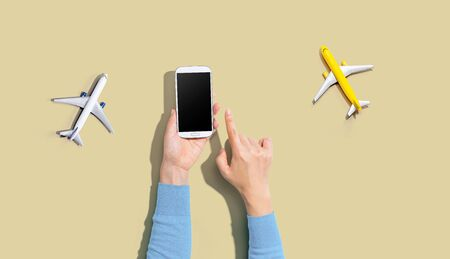 Person holding a smart phone with airplanes from above
