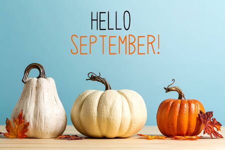 Hello September message with pumpkins on a blue background