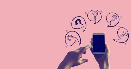 Question marks with speech bubbles with person holding a white smartphone