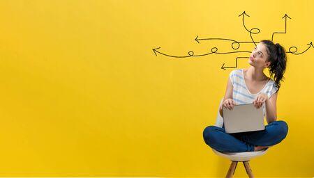 Idea arrows with young woman using a laptop computer Foto de archivo - 129444632