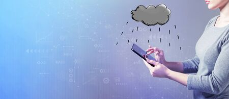 Rain cloud with business woman using a tablet computer Imagens