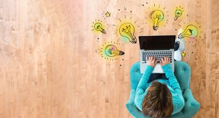 Idea light bulbs with woman using her laptop computer