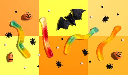 Halloween objects with gummy worms - overhead view flat lay