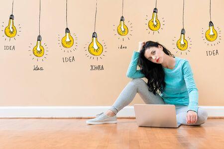 Idea light bulbs with young woman using a laptop computer Фото со стока - 129410807