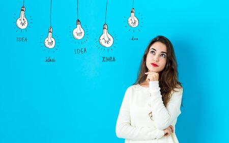 Idea light bulbs with young woman in a thoughtful face Banco de Imagens - 129938355