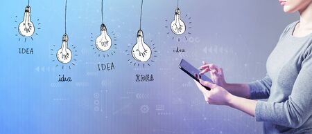 Idea light bulbs with business woman using a tablet computer