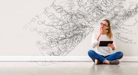 Confused concept with young woman holding a tablet computer Imagens