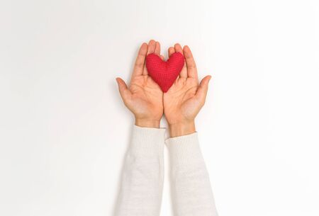 Young woman holding a big Valentines day heart on a white background