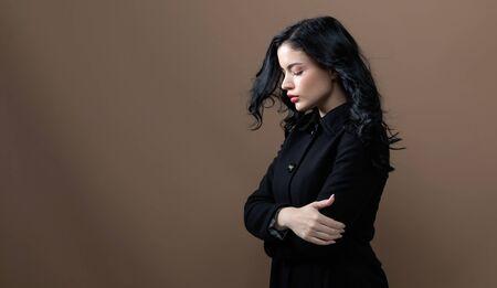 Bella giovane donna in un cappotto alla moda su uno sfondo marrone Archivio Fotografico