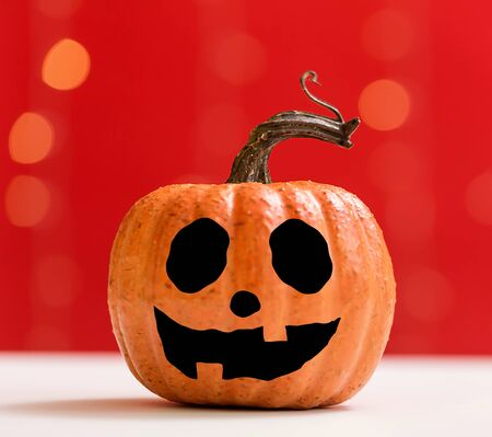Halloween pumpkin on a shiny light red background Stok Fotoğraf