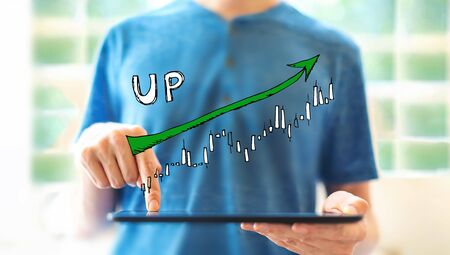 Market up trend chart with young man using a tablet computer