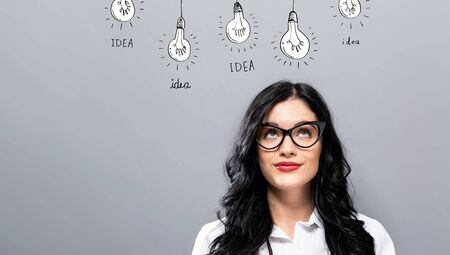 Idea light bulbs with young businesswoman in a thoughtful face Stock Photo
