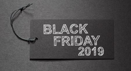 Black Friday 2019 text on a black tag on black paper background Imagens