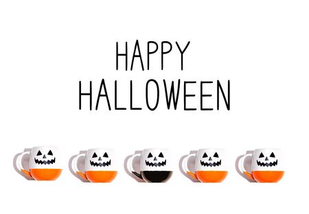 Happy Halloween message with Halloween ghost mugs - flat lay