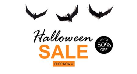 Halloween Sale message with paper bats overhead view on a solid color