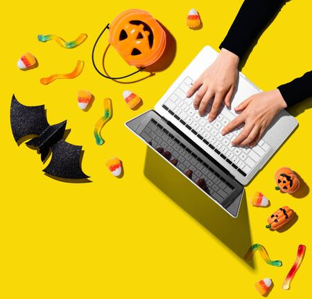 Halloween decorations with person using a laptop computer - overhead view flat lay