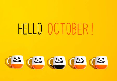 Hello October message with Halloween ghost mugs - flat lay Imagens