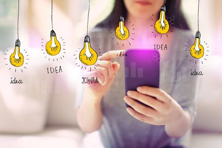 Idea light bulbs with woman using her smartphone in a living room Stock Photo