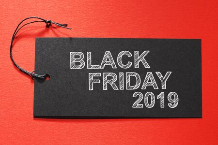 Blank Friday 2019 text on a black tag on a red paper background