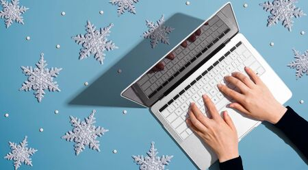 Snowflakes with person using a laptop computer - overhead view flat lay