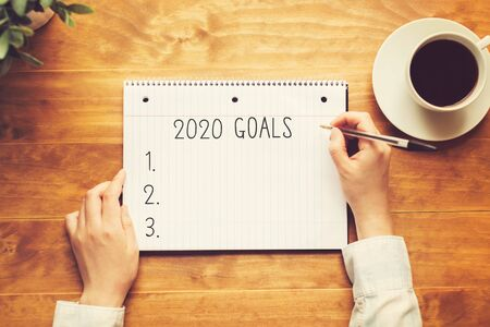 2020 goals with a person holding a pen on a wooden desk