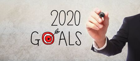 2020 Goals with businessman on gray wall background