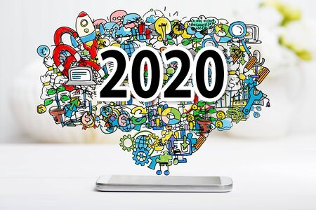 2020 concept with smartphone with illustration on white table Stock Photo