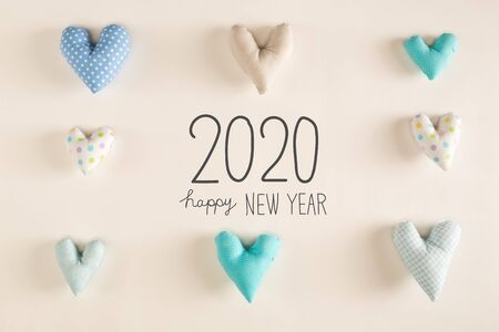 Happy New Year 2020 message with blue heart cushions on a white paper background