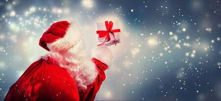 Santa holding a Christmas gift in snowy night Stock Photo