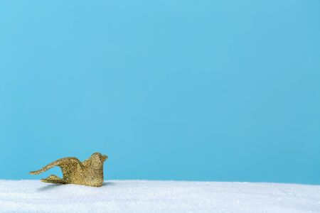 Gold bird ornament in a snow covered landscape Imagens