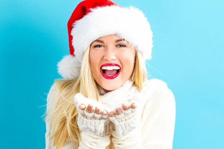 Happy young woman with Santa hat blowing a kiss