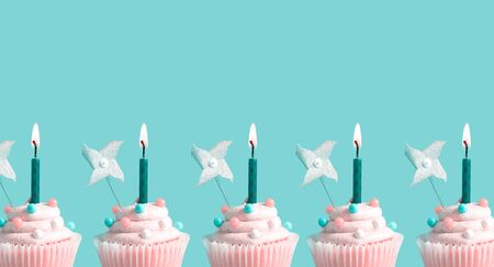 Tasty celebratory cupcakes with decorative lit candles Imagens