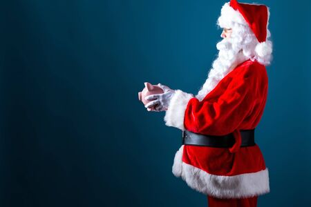 Santa holding a piggy bank on a dark blue background