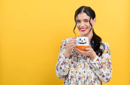 Young woman holding a pumpkin styled coffee mug on a yellow background Imagens