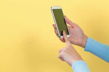 Woman using her smartphone on a yellow background