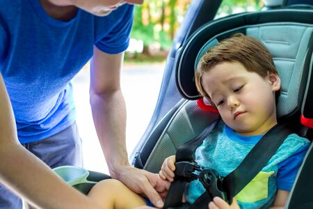 Toddler boy buckled into his car seat by his father