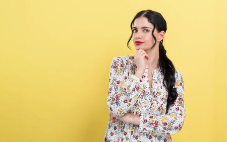 Young woman in a thoughtful pose on a yellow background