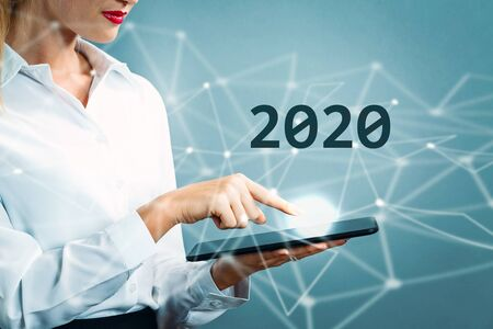 Texto 2020 con mujer de negocios usando una tableta