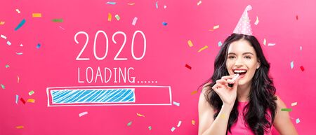 Loading new year 2020 with young woman with party theme on a pink background Stock Photo