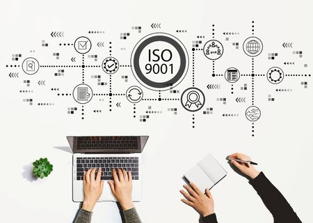 ISO 9001 with people working together with laptop and notebook Stock Photo