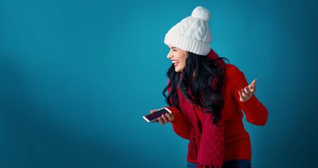 Young woman with Christmas theme using her phone on a blue background