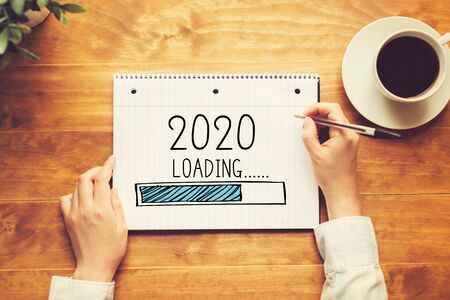 Loading new year 2020 with a person holding a pen on a wooden desk Stock Photo